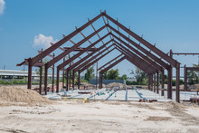 Steel Structure Of New Industrial Building Under Cloud Blue Sky. New Technology Structural Frame Beam Of Factory In Construction. Steel Frame Manufacturer And Pile Of Sand And Gravel In Crosby, TX, US