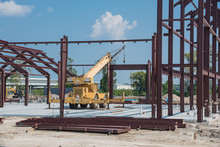 Steel Structure Of New Industrial Building Under Cloud Blue Sky. New Technology Structural Frame Beam Of Factory In Construction. Unfinished Steel Frame Manufacturer And Telescopic Crane, Sand, Gravel
