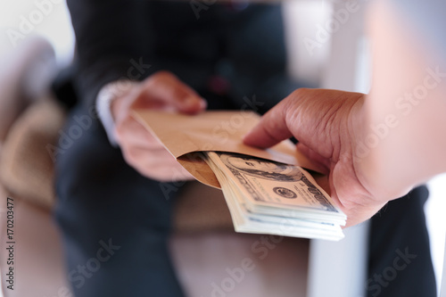 Fotografía Businessman receive money under the table - anti bribery and corruption concepts