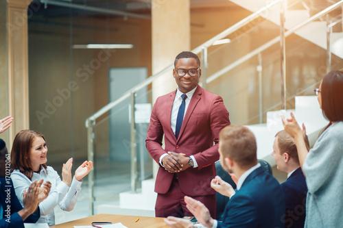 Fotografiet  smiling black male boss talking to business team