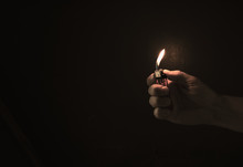 Hand Holding A Lighter In The Dark