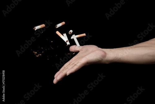 Hand throwing cigarette with motion freeze on black background , no smoke stop q Tablou Canvas