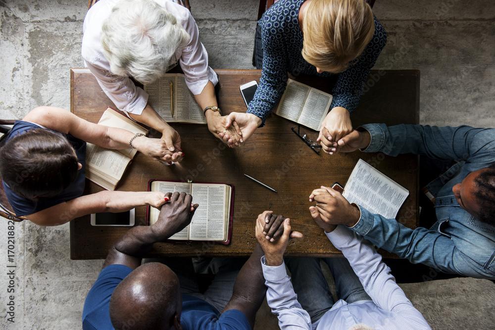 Valokuva  Group of people holding hands praying worship believe