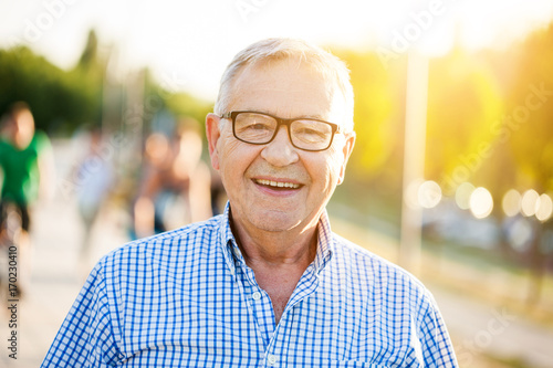 Obraz Outdoor portrait of happy senior man who is looking at camera and smiling. - fototapety do salonu