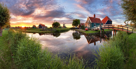 Panorama landscape windmills on water canal in village. Colorful spring sunset in Netherlands, Europe