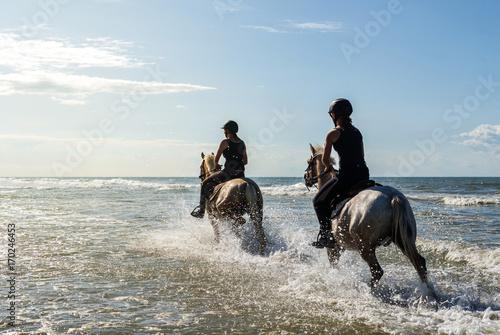 La pose en embrasure Equitation 2 cavalières au galop dans la mer