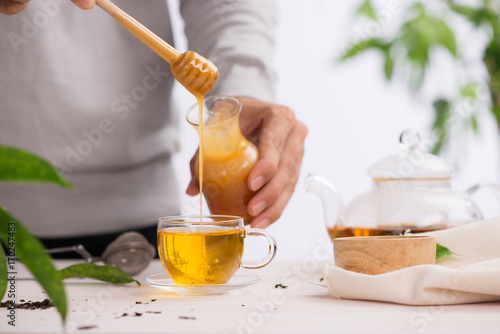 Photo Cropped image of arista pouring honey into cup of tea
