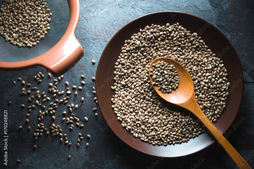 Fototapety, obrazy: Hemp seeds on a plate and in a sieve on a gray blue stone