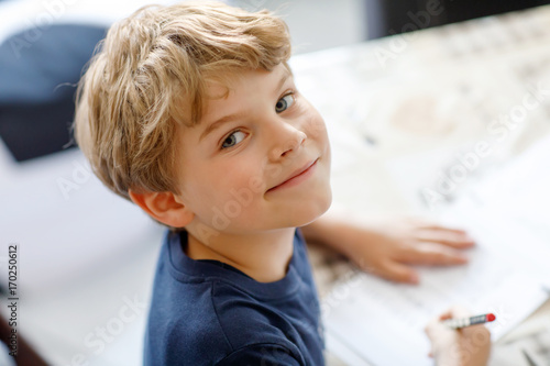 Cuadros en Lienzo Happy smiling kid boy at home making homework writing letters with colorful pens