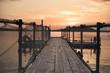 Wooden bridge on the beach and beautiful sunset near the sea