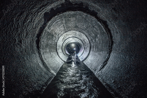 Cadres-photo bureau Canal Diggers are exploring underground river flowing in round sewer tunnel