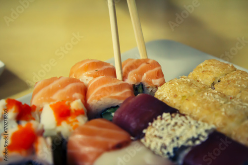 Poster Sushi bar Different sushi rolls with chopsticks on wooden desk