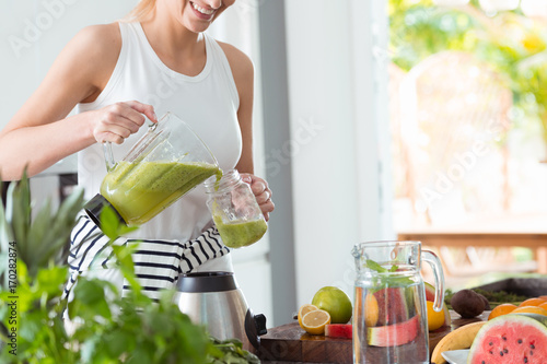 Woman pouring cocktail to glass