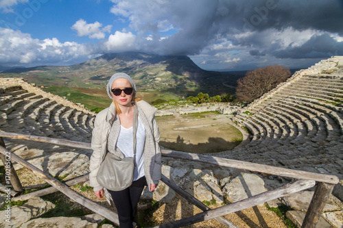 Fotografie, Obraz Female tourist taking photo in front of greek theater of Segesta, Sicily, Italy