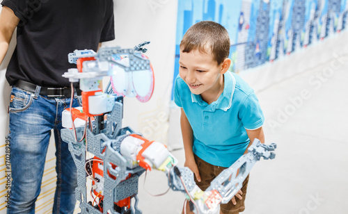 a little boy is talking and in touch with an anthropoid robot Canvas Print