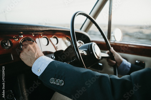 inside view of classic luxury car being driven by man. © daviles