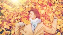 Beautiful Happy Woman Lying On Autumn Leaves