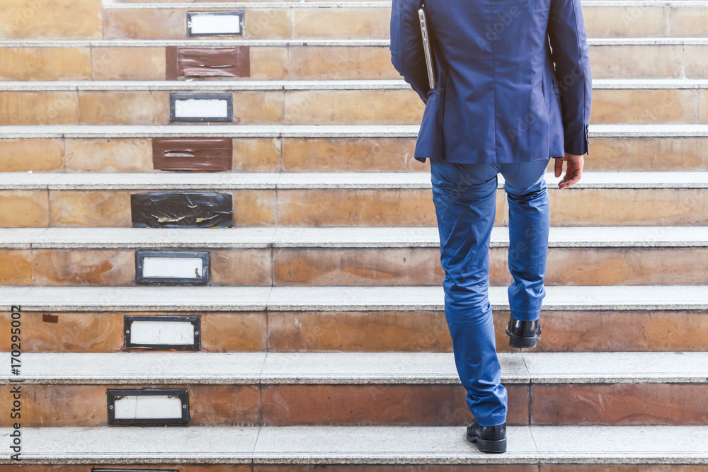 Fototapety, obrazy: Businessman walking up the stairs
