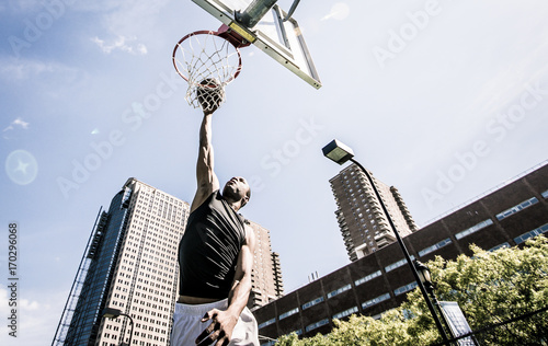 Photo  Basketball player making huge slam dunk
