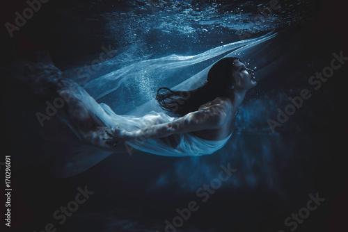 Fotografia  Beautiful woman swimming with fancy dress underwater