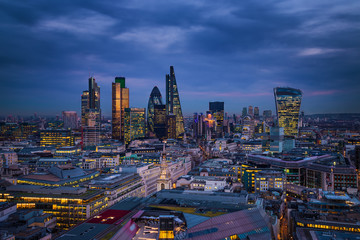 London, England - Panoramic skyline view of Bank district of London with the skyscrapers of Canary Wharf at the background at blue hour