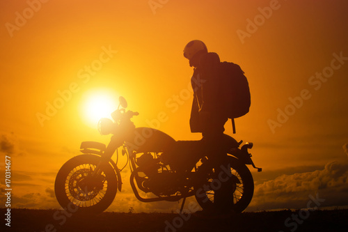 Fotografia  Silhouette of biker man  with his motorbike,he shoulder backpack
