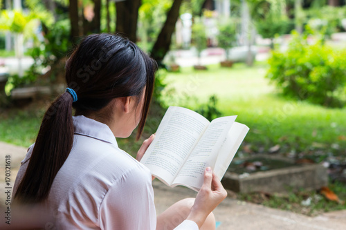 Deurstickers Woman reading book with blurry park background