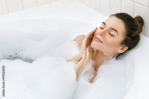 Photographie Woman is taking bath with a foam