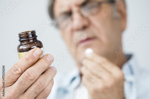 Obraz Old man taking a pill - fototapety do salonu