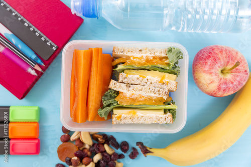 Papiers peints Assortiment School lunch box with sandwich, vegetables, water, nuts and fruits on turquoise background. Healthy eating habits concept