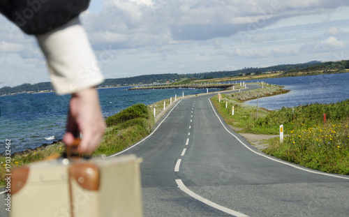Fototapeta Senior Woman travelling on the road with her suitcase through the beautiful nature landscape with water at both sides. obraz na płótnie