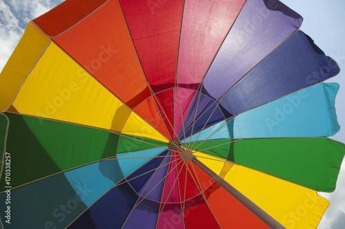 Spoed Fotobehang Luchtsport Looking up into colorful backlit beach umbrella.