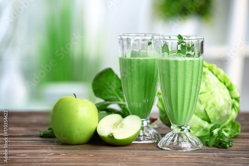 Photo  Glasses of green healthy juice with ingredients on wooden table