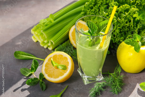 Photo  Glass of green healthy juice with fruits and vegetables on table
