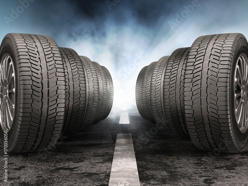 Fotografía Car tires standing on the road against light of headlights.