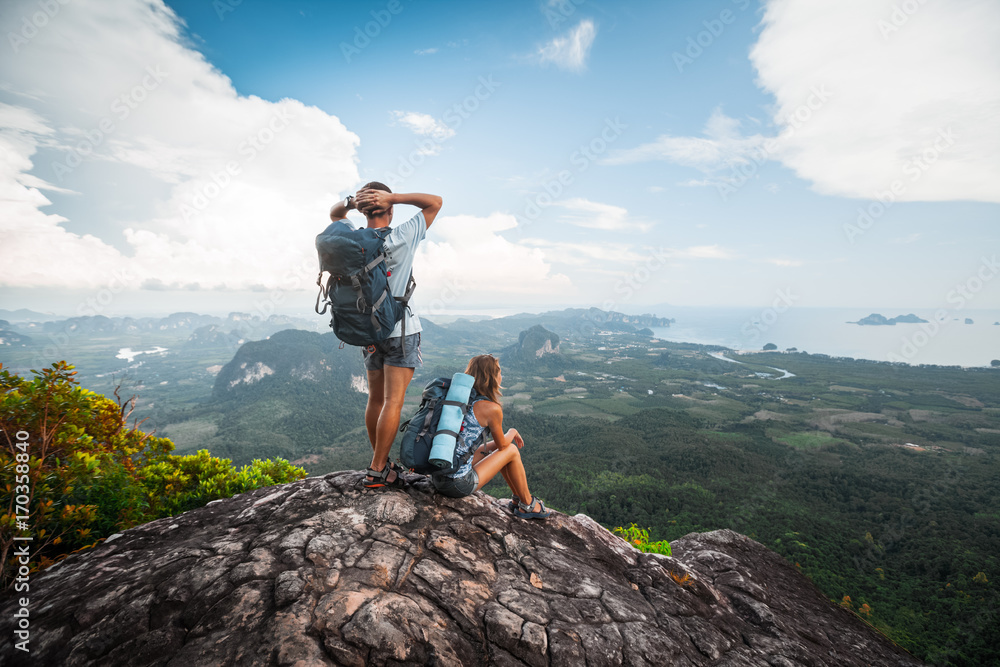 Fototapety, obrazy: Two hikers relax on top of a mountain with great view