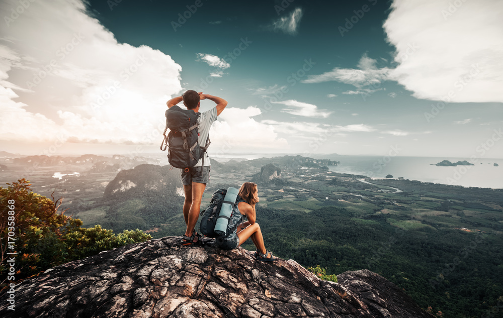 Fototapety, obrazy: Hikers relax on top of a mountain and enjoy valley greate view