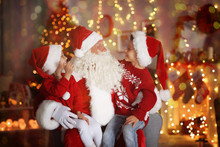 Cute Little Boy And Girl With Santa Claus In Room Decorated For Christmas