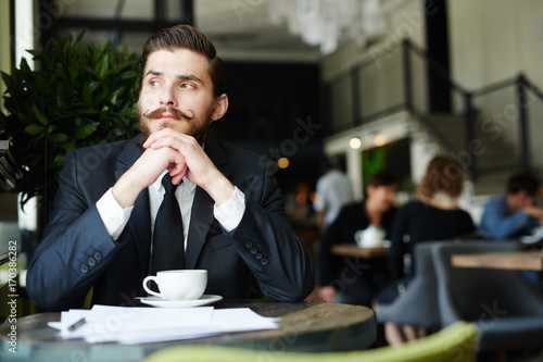 Photo Pensive businessman sitting in cafe by cup of coffee at break