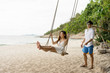 couple happiness with wooden swings on the beach