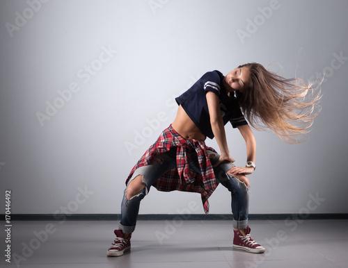 mloda-kobieta-w-krotkiej-koszulce-tanczaca-taniec-nowoczesny-na-szarym-tle