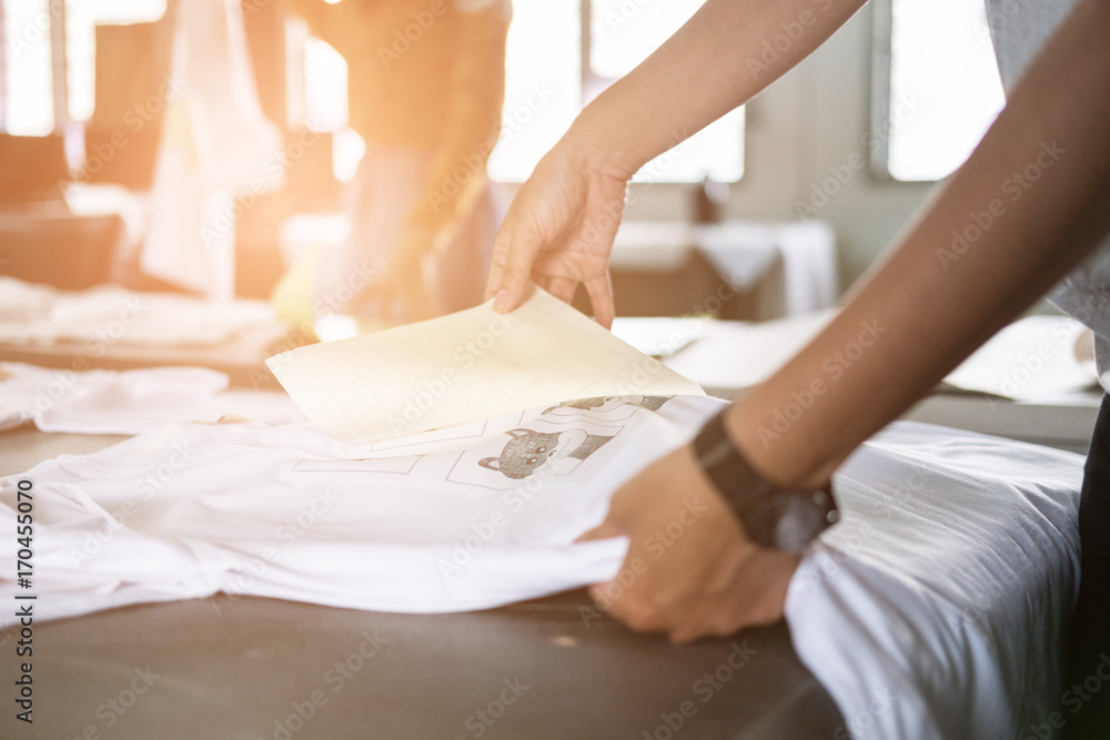 Fototapety, obrazy: Young woman pull out paper from waterproof film on fabric at shop. worker working on manual screen printing on t-shirt.
