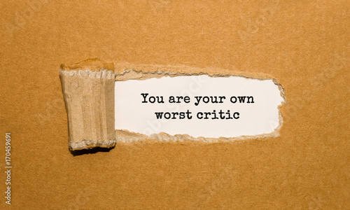 Fotografía The text You are your own worst critic appearing behind torn brown paper