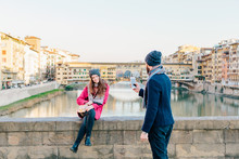Boyfriend Taking Photo Of Girlfriend And The Old Bridge In Florence