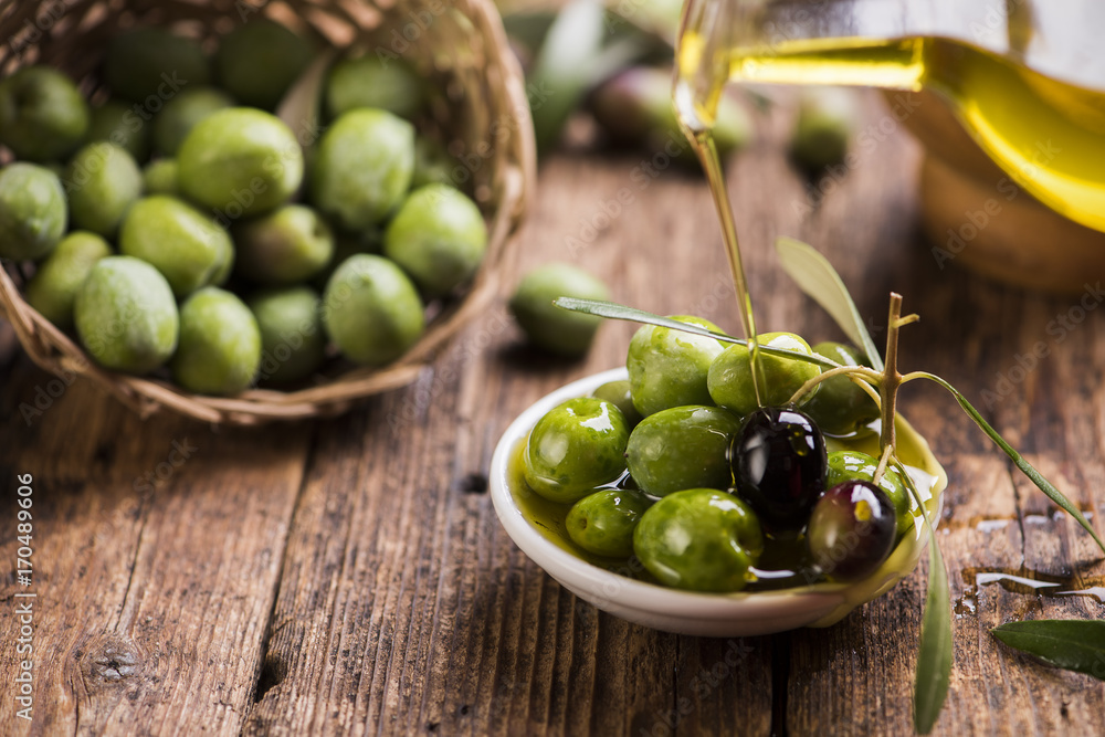 Fototapety, obrazy: Bottle pouring virgin olive oil in a bowl close up