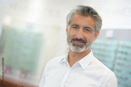 portrait of handsome optician in his store Canvas Print
