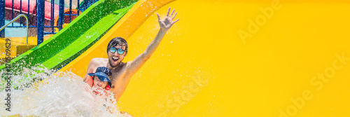 Staande foto Amusementspark BANNER Father and son on a water slide in the water park Long Format