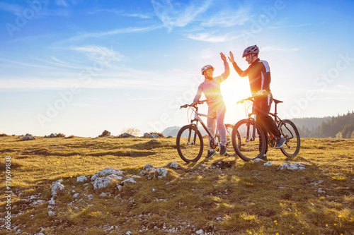 Foto  happy couple goes on a mountain asphalt road in the woods on bikes with helmets