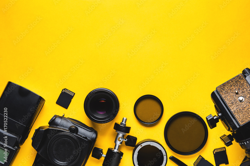 Fototapety, obrazy: Digital camera, lenses and equipment of the photographer on a yellow background
