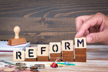 Reform Concept. Wooden Letters On The Office Desk, Informative And Communication Background.